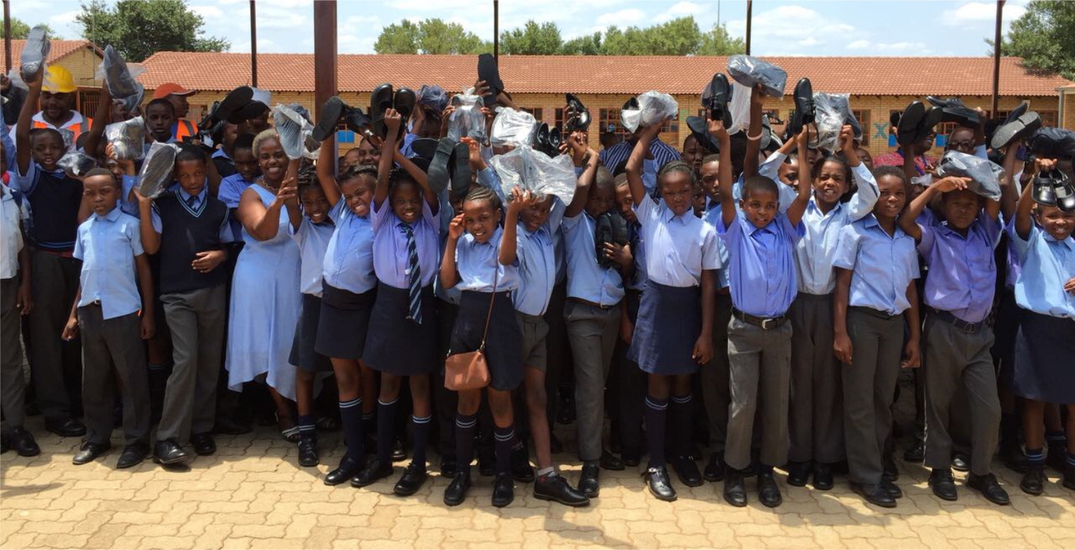 Elated children of Mahlasedi Masani Primary School in Mamelodi holding up their new school shoes that CONCO donated.